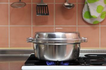 「煮る」、「ゆでる」、「炊く」「焼く」、「蒸す」、「炒める」、「揚げる」、「オーブンとして使う」など、なんと8役も果たしてしまう「生活春秋」の無水鍋。無駄をそぎ落とした飾り気のないかたちは、羽釜をヒントに作られました。本体、蓋ともに、熱伝導率に優れた厚手のアルミ合金でできており、中を密閉状態に保つため、その名の通り、素材の水分だけで調理することができます。とても丈夫で耐久性に優れているので、一生モノどころか、親子2代に渡り愛用している人も。一度その良さを知ると、どうしても誰かに薦めたくなってしまう、まさに魔法のお鍋です。
