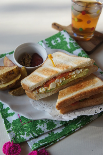 アボカドと刻んだゆで卵をスモークサーモンと一緒に食パンで挟んだごちそうサンドイッチ。休日のブランチや、ピクニックのお弁当にもおすすめです。