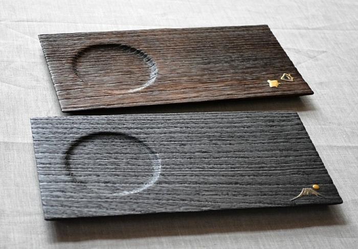同じ木製プレートでも、こちらは和の装いのちょこっとトレー。桐の木面に焼き加工をほどこした「焼桐」という手法で作られた素朴で懐かしい質感です。茶托のようにくぼみがあるので、持ち運ぶ時も安定します。カフェトレーとして使う他、和の小物やグラスに生けた草花を置く花器としても使えます。