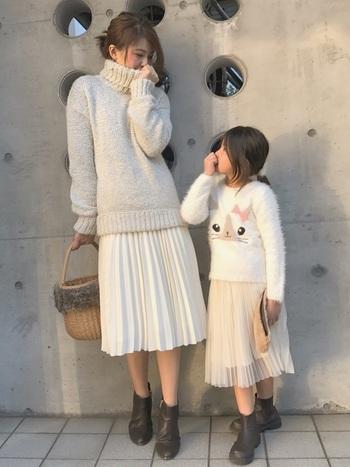 明るいカラーのニットに、やわらかい素材の白のプリーツスカートをプラス。ファー付きのかごバッグや、焦げ茶色のブーツで、全体のバランスを取っています。