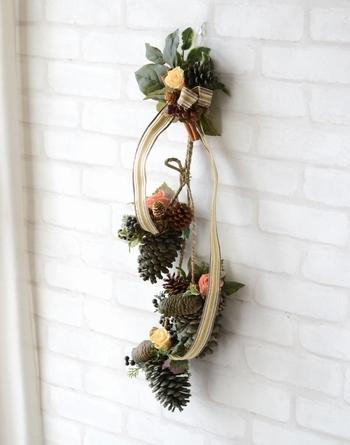 プリザーブドフラワーの壁飾りハンギングに松ぼっくりを使ってもナチュラルでオシャレ。組み合わせるお花やリボンの色でもっとクリスマスにアレンジできますね。