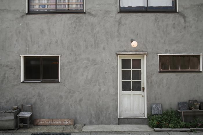 コンクリートの灰色が風景に溶け込んで、通り過ぎてしまいそうなさりげなさ。 小さなドアの上の丸電球がかわいい目印です。