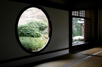 """京都の北側・鷹峯(たかがみね)にある「源光庵」は、二つの窓でよく知られています。写真手前の""""悟りの窓""""といわれる丸窓と、奥に見える""""迷いの窓""""の角窓。四季折々の風景を切り取る窓は、まるで自然が織りなす掛け軸のような風情を感じさせます。とくに純白の雪景色は心が洗われるような清廉さです。"""