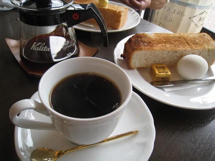 Aセットのライ麦パンの厚切りトーストとコーヒー。添えられたバターは塗りやすいように温めてあります。テーブルにある、シナモンシュガーを振りかけて頂くとさらに美味しいですよ。