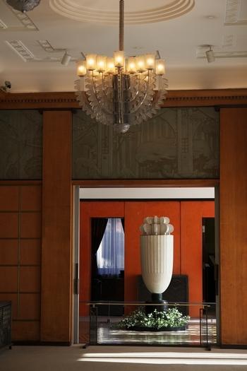 大客室には、同じくルネ・ラリック作のシャンデリアが。 また、奥に見えるのはフランスのデザイナーであるアンリ・ラパン作の香水塔です。朝香宮邸時代には、上部の照明部分に香水を施し、照明の熱で香りを漂わせたといわれています。 幾何学的にデザインされた花が主なモチーフとなって、細部にまでわたる細かなレリーフとシンメトリーのデザインが本当に美しい空間です。