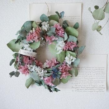優しいピンクとホワイトのお花がアクセントになったスモーキーでナチュラルな風合いのドライリースです。