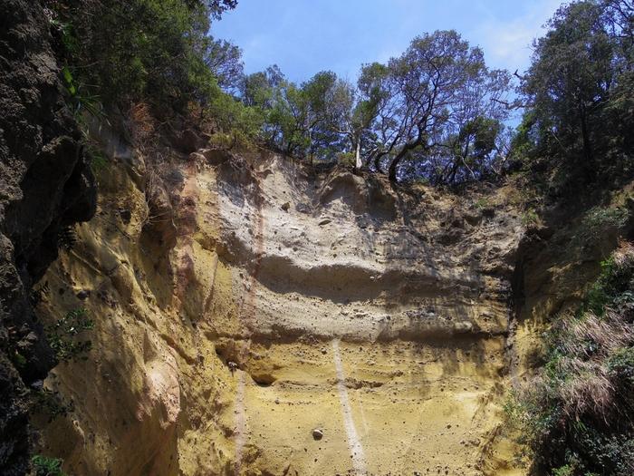 黄褐色が青い空に映える、洞窟の壁。