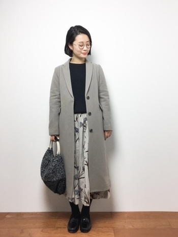 ひざ下~くるぶしくらいの、中途半端な丈感のコートには、コートよりも少し長めのスカートを合わせることでバランスを取りましょう。色味もモノトーンなど同色で揃えると落ち着いた雰囲気に。スカートにお好みの柄モノを取り入れると、大人っぽさの中にもかわいさを演出できます。