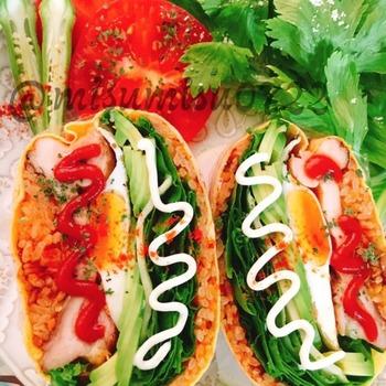 通常のおにぎりらずは最後に海苔を巻きますが、こちらは海苔のかわりに薄焼き卵を巻いて。中身をチキンライスにすればオムライスおにぎらずの完成です♪しかもこちらのレシピならチキンライスも炊飯器で炊きこむのでとても簡単。野菜も一緒にたっぷり挟んでいただきましょう!