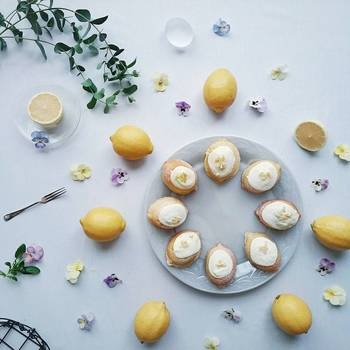 レモンケーキをまるいお皿にきれいに並べて。そのまわりを囲むようにフレッシュレモンとビオラの花を散りばめて。まるでケーキをデコレーションするかのように美しく飾られたテーブルが素敵です。