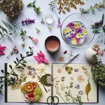 ノートにハサミ、ピンセット。押し花づくりのワンシーンのようなデコレーション。生花だけでなく、プリザーブドフラワーや押し花など、いろいろな種類のお花をシーンに合わせて使う flit (ふりっと) さん のセンスが光ります。