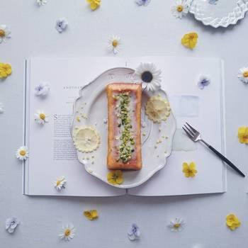 曲線的なお皿にのせた、長方形のウィークエンドシトロン。その下にしかくい本を敷いて。お花の形にカットされたレモンと、まわりに散りばめられたビオラとノースポール。曲線と直線の対比が素敵な一枚です。