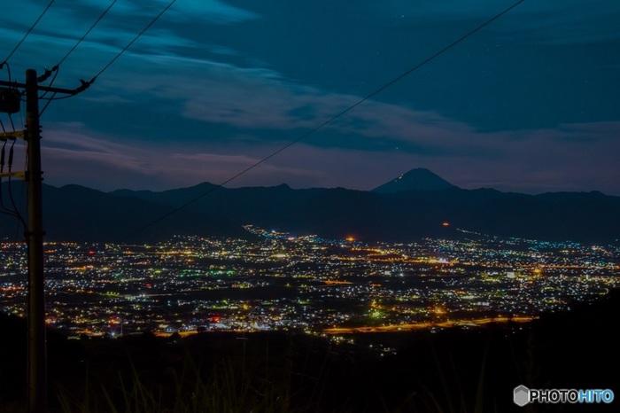 日が落ちるとそこには、盆地に広がる夜景が一面に登場します。同じ場所にいても、空の色や盆地の風景、富士山の陰りや存在感など、ちょっとした悩みを全部吹っ飛ばしてくれるような素晴らしい景色がそこには広がっています。
