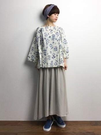 ちょっぴり春の軽さも感じられるスカートスタイル。ブラウスの花柄とスニーカーのカラーを合わせている上級テクニックです。