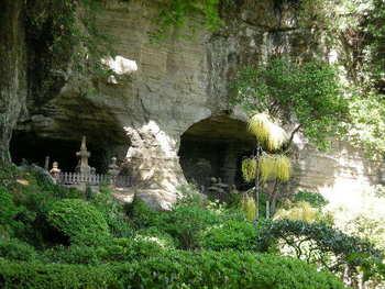 """新緑と岩肌の鎌倉らしい景色。岩壁に見えるのは、足利一族の墓と伝えられる""""やぐら""""。 (""""やぐら""""とは、鎌倉周辺で散見される、鎌倉時代中期以降から室町時代前半にかけて作られた横穴式の納骨窟のこと。)"""