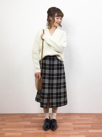 ホワイトニットを可愛らしく着こなすなら、チェック柄スカートがおすすめ。子どもっぽくならないように、ルーズな髪型やメイクで大人っぽさを出しましょう。