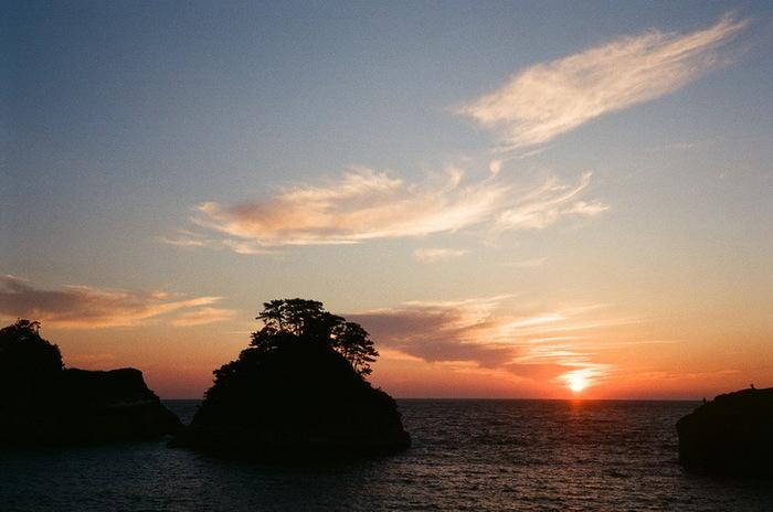 """「黄金崎」や""""伊豆の松島""""と称される「堂ヶ島」でよく知られる「西伊豆」。  複雑な海岸線や小島、遠くに望む富士山等の自然が織り成す景色もさることながら、「日本一の夕陽」が眺められることでもよく知られています。特に、マジックアワーと呼ばれる日没後の一時の景色は、幻想的で言葉には表せない美しさがあります。  今記事では、マジックアワーの一時に、西伊豆の海岸で撮影された素晴らしい景色の数々を、沼津方面から南下しながら紹介します。  伊豆を訪れるのなら、ぜひマジックアワーの幻想的な一時も味わって下さい。きっと忘れられない光景になるはずです。"""