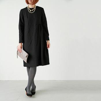 ミニマルなデザインのブラックドレスにグレータイツ。上品でありながら、モードな雰囲気も漂います。