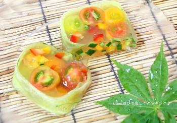 見ているだけで涼し気な夏野菜のテリーヌ。パウンドケーキ型を利用して、プチトマトやパプリカ、キューり、色とりどりの夏野菜をコンソメ風味の寒天液で固めました。ガラスのプレートにお洒落に盛り付ければ、より一層夏を感じられますね。