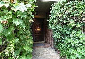 立地はアイビー通り(青学会館の前)。お茶の水の聖橋や日本武道館を設計したモダニズム建築家・山田守氏の旧邸ピロティ部分に増築され、1988年にオープンした喫茶店です。生い茂る蔦を抜けて玄関へ。