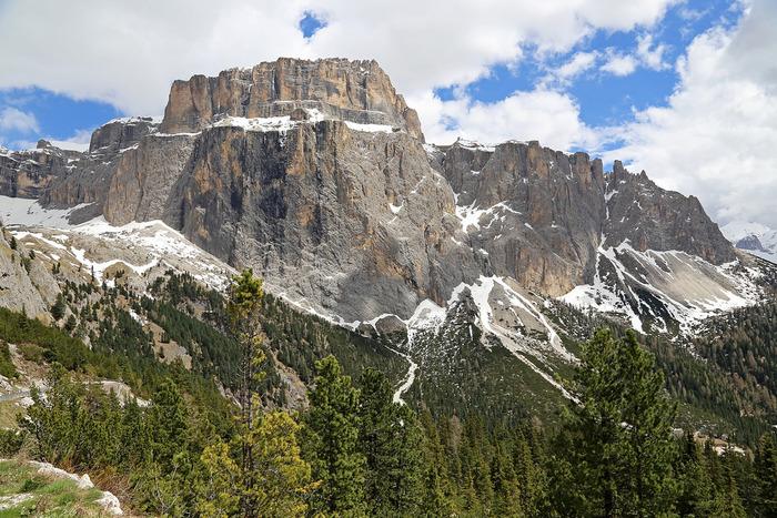 標高2000メートル級の山々が連なるドロミテでは、東アルプスならではの雄大な景色を臨むことができます。垂直に立ちはだかる断崖、夏でも残雪が残る山頂、山麓に広がる緑の森が融和した自然美の素晴らしさから、ドロミテは世界自然遺産に登録されています。