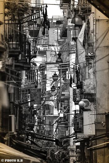 上空から眺めると、碁盤目のように整然とされたナポリ旧市街には、独特の下町らしい風情が漂っています。石畳が敷かれた路地の両横に立ち並ぶ建物には、洗濯物を干すための紐が繋がれており、古き良き下町情緒を醸し出しています。