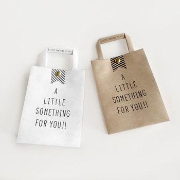 ちょっとした贈り物にぴったりな「LITTLE SOMETHING」ミニショッパー。カラーはホワイトとクラフトの2色。ホワイトは表面は白、内側は茶色になっています。ストライプの帯と金の割りピンがいいアクセントに。