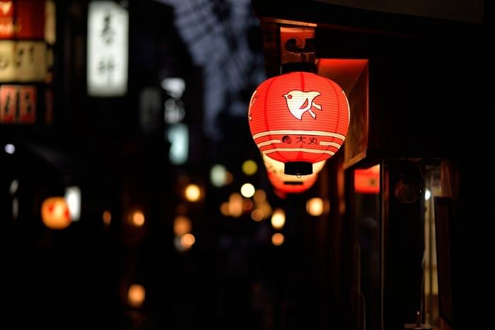 """京都市内中心部にある繁華街、河原町から少し足を伸ばすとそこは花街の通り。昼間はたくさんの人が往来して""""ザ・観光地""""といった風景ですが、夜のとばりが落ちるとぽつぽつとお茶屋さんや料亭のぼんぼりが灯り始め、なんともいえない雰囲気に。こんな夜の街並みが楽しめるのも京都の魅力ですね。"""