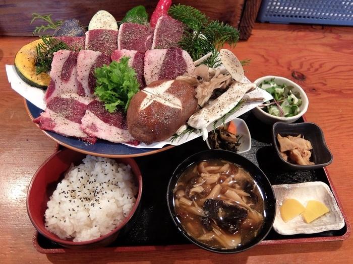 「熊焼き肉定食」 熊肉、野菜、キノコのみそ汁、ご飯、ひじきの煮物、お漬物など・・・。 熊肉は、鹿や羊よりも脂がのっているけれどもお肉は少しかため。 豚鶏牛で言えば牛に近いそうです。クセはあまり無くて食べやすいとのこと。