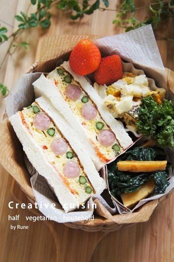 トマトとアスパラ、ウインナーと彩り豊かなスパニッシュオムレツのサンドイッチ。具沢山で食べ応えがあり、断面の美しさも見どころですね。春のピクニックメニューにもぴったりです。