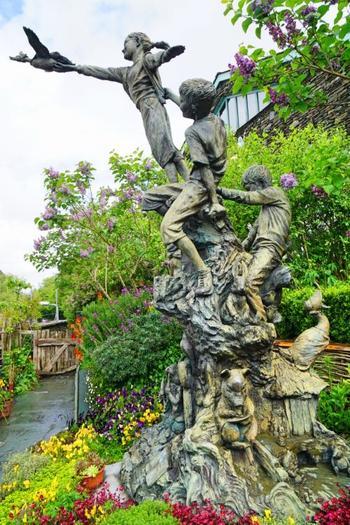 ピーターラビットガーデンに設置された3人の子供ブロンズ像。像を取り巻くように咲く美しい花々が見られます。