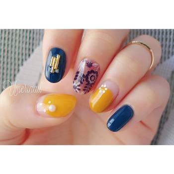 色鮮やかな北欧風ネイル。イエローとブルー、花柄のオレンジが相性よく、かわいらしい仕上がりです。