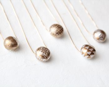 日本の伝統工芸を活かしたモノづくりを続ける「KARAFURU(カラフル)」のネックレス。  ころんとした大粒の淡水パールに24金で「蒔絵(まきえ)」を施した、伝統工芸の職人技が光る芸術品。蒔絵とは漆のお椀などの模様に使われる技法。漆を使って絵描き、乾く前に金粉などを定着させる技です。  5種類ある伝統の和柄の文様にはそれぞれ「魔除け」「長寿」などの意味やストーリーがあり、お守り代わりに身に着けてもいいですね。