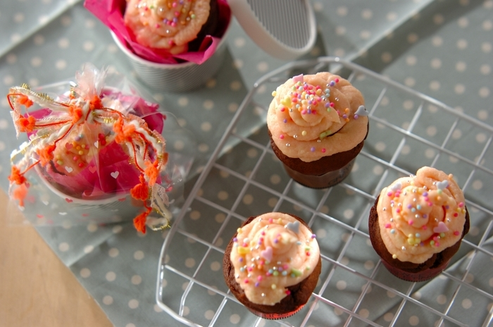 【バレンタインカップケーキ】 ピンクのクリームチーズフロスティングを使った見た目も可愛いいカップケーキ。 焼き上げたカップケーキを、ペーパーナプキンを敷いた紙コップにポンッと入れて、リボンを結べば簡単ラッピングの出来上がり!
