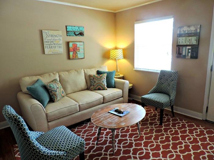 白とブルーのインテリアが基調のお部屋も、電球色のテーブルランプとレンガ色のラグで温かみを感じるお部屋に。全体を暖色系にしていないから、空間の広さがそのまま活かされています。