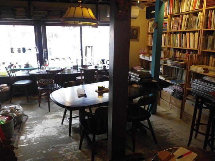 通りに面した窓から木漏れ陽が差し込み、本、珈琲、お菓子、アンティーク雑貨などさまざまなモノと香りがあふれる店内。壁一面に置かれた本は店内で読めるだけでなく、販売もしています。