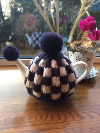 市松模様が特徴のこちらの作品は、編み地が厚く保温力抜群!埃よけにもなるお揃いの注ぎ口にさすポンポンがキュートです。