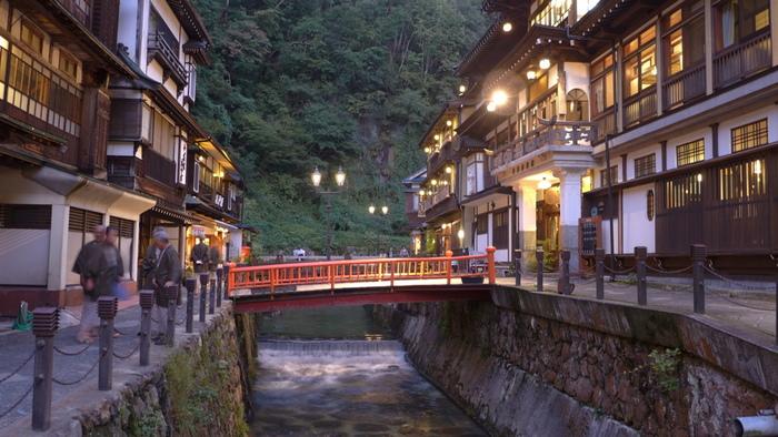 緑に囲まれた銀山温泉。中央を流れる銀山川の両岸に沿って、大正末期から昭和初期に建設された歴史ある木造の宿が軒を連ねています。
