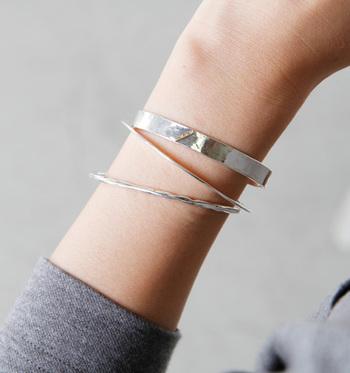 """""""身につける人が自由な発想で、気持ちよく、楽しくいられるジュエリーを…""""と2009年にスタートした「lilojewelry(ライラジュエリー)」。シンプルなシルバーのブレスレットは、重ねるとより華やかで印象的。スタイリッシュで洗練された雰囲気になりますよ。太いシルバーのブレスレットには、さりげなく4つのダイヤモンドがあしらわれたモチーフが付いていて、ポイントになっています。"""