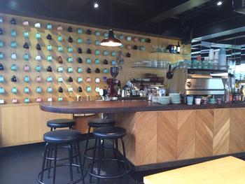 壁一面にコーヒーカップがディスプレイされ、屋台をイメージした車輪のついたカウンターテーブルが独創的でかっこいい!お店には焙煎所も併設されています。