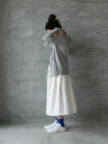 白のリネンスカートにパーカーとスニーカーを合わせて。カジュアルさもありながら、きちんと女性らしさも感じる素敵なコーディネートですね。差し色の青の靴下がポイントになって◎。