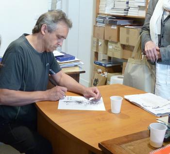 オフィスでペンを走らせるリュバロ。ブーケの線画が描かれた原稿に手を入れている様子です。