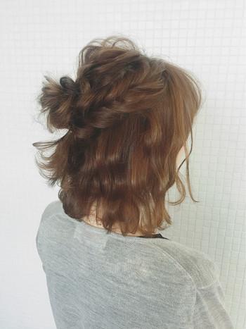 トップにお団子をつくり、サイドは編み込みに。仕上げに指先で毛束をちょんちょんと出せば完成です。