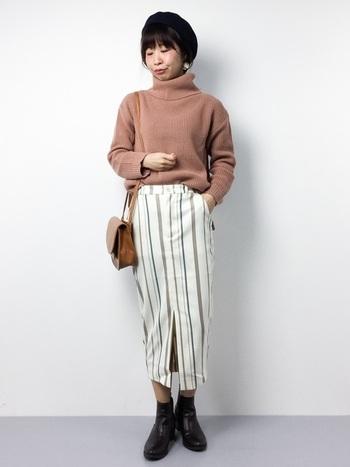 ふんわり柔らかなピンクのタートルニットと、白のタイトスカートを合わせた、メリハリのある着こなし。縦のストライプ柄なら、脚長効果も期待できますよ。