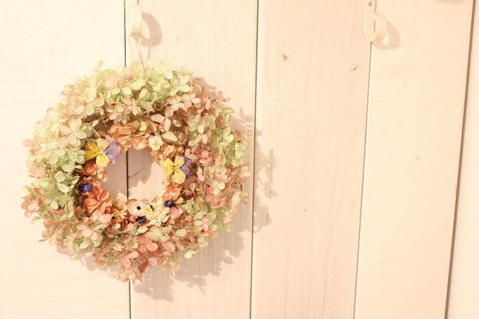 こちらのリース、実は二重になっています。色鮮やかな中央のリースに紫陽花のリースを外側にかぶせました。小さなお花がたくさんついて、まるでちょうちょが止まっているようにも見えます。壁に映る影もキュートですね。