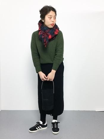 モスグリーンのニットと赤のチェックストールのコントラストが印象的なシンプルなスカートスタイル。立体的にストールを巻くと、小顔効果も期待できますよ。