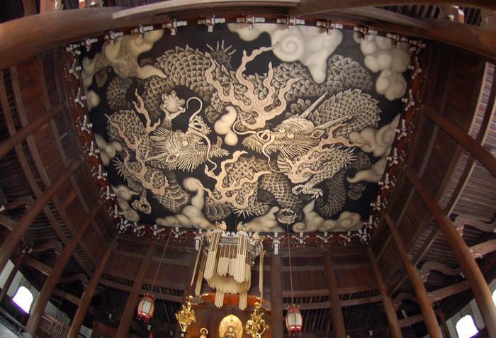 """【法堂の天井に描かれた、建仁寺開創800年を記念して2002年に完成した小泉淳作筆『双龍図』。大きさは、畳108枚分にも及ぶびます。""""龍""""は、仏法を守護する八神の一つで、禅寺の法堂にはよく描かれています。】"""