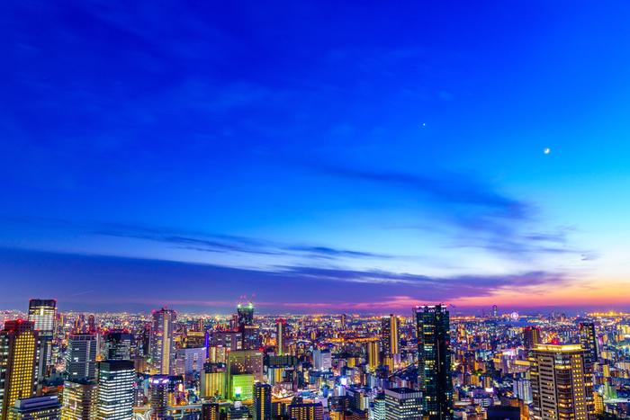 そして、その青い星の海の下に広がるの大阪の街。無秩序でクリアな光が創り出すシャープな立体感は、まるで、デジタル世界の街並みのようです。