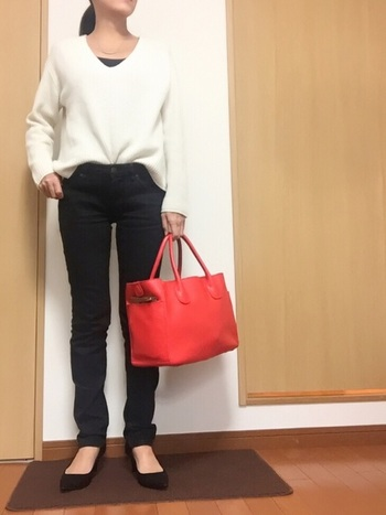 ホワイトのカシミヤブレンドVネックセーター。オレンジの大きなバッグをアクセントに大人の着こなし。ゆるめシルエットなのでタックインはお約束。
