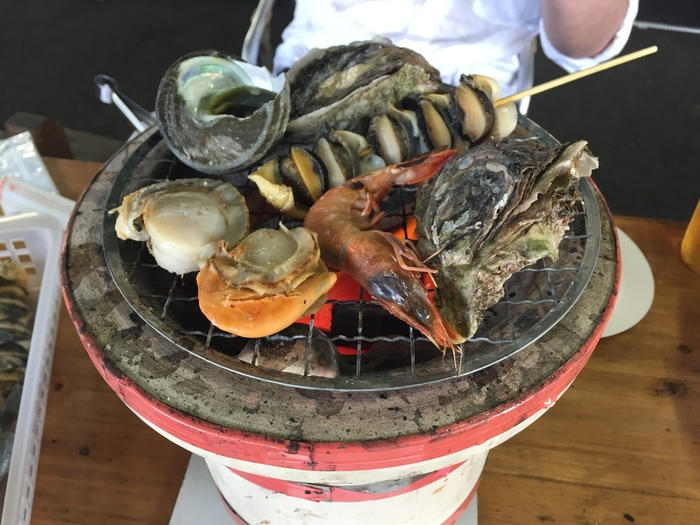 大島にある「道の駅 よしうみ いきいき館」では、来島海峡で獲れた新鮮な魚介類を炭火で焼いて食べる「海鮮七輪バーベキュー」がとても人気です。鮮魚コーナーで好きな魚介を選んで自由に焼くスタイル。予算に合わせて楽しめます。